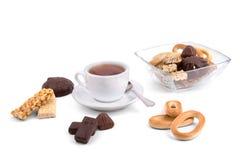 Weiße Tasse Tee und eine Auswahl von Bonbons Stockfotos