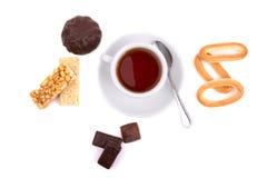 Weiße Tasse Tee und eine Auswahl von Bonbons Lizenzfreies Stockfoto