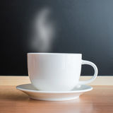 Weiße Tasse und Untertasse auf hölzerner Tabelle Lizenzfreies Stockbild