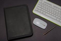 Weiße Tastatur auf einem schwarzen Hintergrund mit ledernem Ordner und Stift Ansicht von oben stockbilder