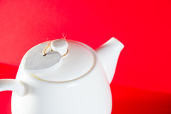 Weiße Teekanne mit dem Herzen gebunden mit einer Schnur lokalisiert auf rotem Hintergrund Liebestee Lizenzfreies Stockfoto