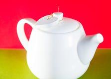 Weiße Teekanne mit dem Herzen gebunden mit einer Schnur lokalisiert auf rotem Hintergrund Liebestee Lizenzfreie Stockfotografie