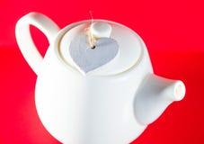 Weiße Teekanne mit dem Herzen gebunden mit einer Schnur lokalisiert auf rotem Hintergrund Liebestee Stockfotos
