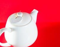 Weiße Teekanne mit dem Herzen gebunden mit einer Schnur lokalisiert auf rotem Hintergrund Liebestee Stockbild