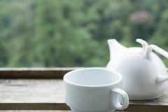 weiße Teeschale und -becher auf hölzerner Tabelle mit grünem Naturhintergrund Lizenzfreie Stockfotografie