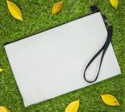 Weiße Textiltasche auf Grashintergrund Leere Gewebetasche für Entwurf lizenzfreies stockfoto
