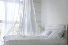 Weiße themenorientierte Bettlaken und weißer Vorhang morgens, Schlafzimmerinnenraum stockfoto