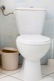 Weiße Toilette in der Badezimmertoilette und in wenigem Abfalleimer Stockbilder