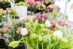 Weiße Tulpen und Bündel der farbigen Blumen in einem Markt lizenzfreie stockbilder
