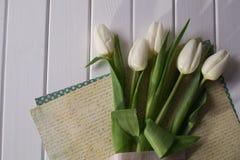 Weiße Tulpen und leeres Papier oder Buchstabe auf weißem Hintergrund Stockbilder
