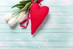 Weiße Tulpenblumen und dekoratives rotes Herz auf Türkis woode Lizenzfreies Stockfoto