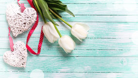 Weiße Tulpenblumen und zwei dekorative Herzen auf Türkis flehen an Lizenzfreie Stockfotos