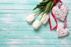 Weiße Tulpenblumen und zwei dekorative Herzen auf Türkis flehen an Lizenzfreies Stockbild
