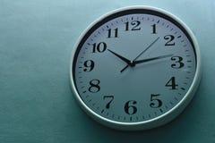 Weiße Uhr auf einer blauen Wand Stockfotografie
