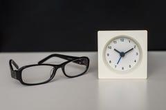 Weiße Uhr auf einer weißen Tabelle gegen den Hintergrund Stockbild