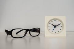 Weiße Uhr auf einer weißen Tabelle gegen den Hintergrund Lizenzfreie Stockbilder