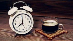 Weiße Uhr 8 O ` Uhr mit Kaffeetasse auf hölzernem Hintergrund Stockfotografie