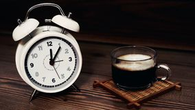 Weiße Uhr 12 O ` Uhr mit Kaffeetasse auf hölzernem Hintergrund Stockfotos