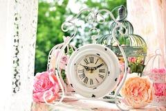 Weiße Uhr und Vogelkäfige der Weinleseart mit Blumen Stockbild
