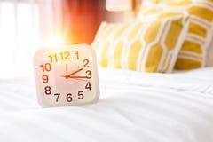 Weiße Uhr und weißes Bett stockbild