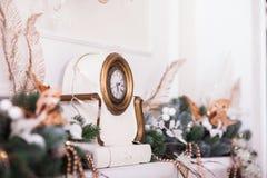 Weiße Uhren mit verzierten Niederlassungen des Weihnachtsbaums Lizenzfreies Stockfoto