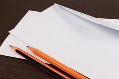 Weiße Umschläge mit Bleistift auf Holztisch Lizenzfreies Stockfoto
