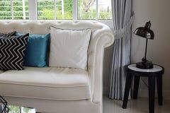 Weiße und blaue Kissen auf einer weißen Ledercouch Lizenzfreies Stockfoto