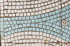 Weiße und blaue Mosaikfliesen mit Bild der Sonne oder der Blume auf der Wand Stockfotografie