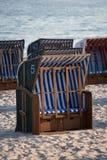 Weiße und blaue Strandstühle auf Sand Stockfotografie