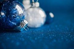 Weiße und blaue Weihnachtsverzierungen auf dunkelblauem Funkelnhintergrund mit Raum für Text Frohe Weihnacht-Karte Stockfoto