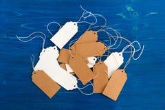 Weiße und braune Preise des leeren Papiers oder Kennsatzfamilie auf dem blauen hölzernen Hintergrund Stockbild