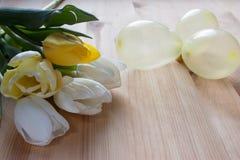 Weiße und gelbe lupans, gelbe kleine Ballone auf einem hellen hölzernen Hintergrund Stockbild