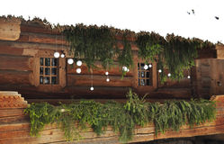 Weiße und grüne Feiertagsdekoration auf einem Portal eines alten Klotzhäuschens mit Fichtenzweigen und Bällen der weißen Weihnach Stockfotos