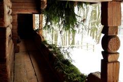 Weiße und grüne Feiertagsdekoration an einem Portal eines alten Klotzhäuschens mit Fichtenzweigen und Bällen der weißen Weihnacht Stockbild