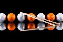 Weiße und orange Golfbälle mit Bambusessstäbchen Lizenzfreies Stockbild