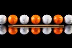 Weiße und orange Golfbälle mit Bambusessstäbchen Stockfotos