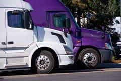 Weiße und purpurrote große LKWs der Anlagen halb stehen auf Fernfahrerrastplatzseite b Stockfoto