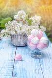 Weiße und rosa Eibische im runden Glasvase mit einem Korb der empfindlichen weißen Flieder Der horizontale Rahmen Stockfoto