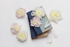 Weiße und rosa Pfingstrosen und alte Bücher auf weißem Hintergrund Lizenzfreie Stockbilder
