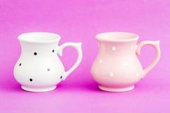 Weiße und rosa Weinlese-Buttermilch-Schalen auf purpurrotem Hintergrund Lizenzfreie Stockfotos