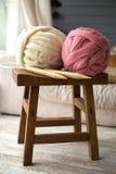Weiße und rosa Wollbälle mit hölzernen Stricknadeln auf Holzstuhl in gemütlichem Stockfoto