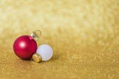 Weiße und rote Mattweihnachtsbälle auf funkelndem goldenem Hintergrund, selektiver Fokus stockfoto