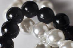 Weiße und schwarze Perlen in einer Halskette stockbilder