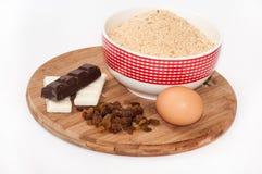 Weiße und schwarze Schokolade, Rosinen, Ei und Grundkeks backen zusammen Stockbild