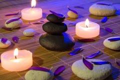 Weiße und schwarze Steine, purpurrote Blumenblätter und Kerzen auf Bambus Lizenzfreie Stockfotografie