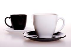 Weiße und schwarze Tasse Tee Stockbild