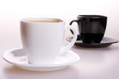 Weiße und schwarze Tasse Tee Lizenzfreie Stockfotos