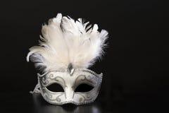 Weiße und silberne venetianische Karnevalsmaske mit Federn auf einem schwarzen Hintergrund Stockfotografie