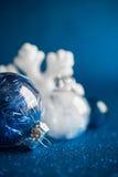Weiße und silberne Weihnachtsverzierungen auf dunkelblauem Funkelnhintergrund mit Raum für Text Lizenzfreies Stockfoto