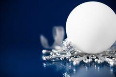 Weiße und silberne Weihnachtsverzierungen auf dunkelblauem Hintergrund mit Raum für Text Lizenzfreie Stockfotografie